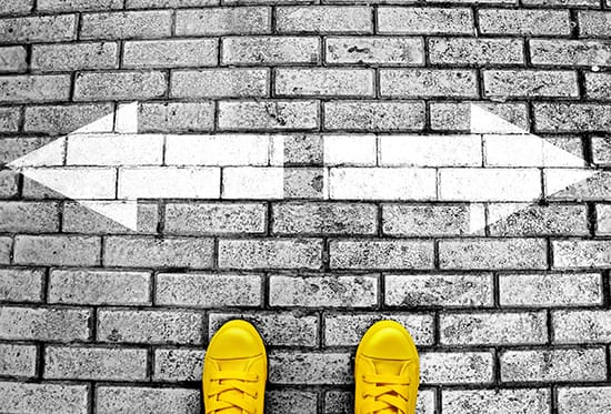 A pair of yellow trainers stand in front of two arrows